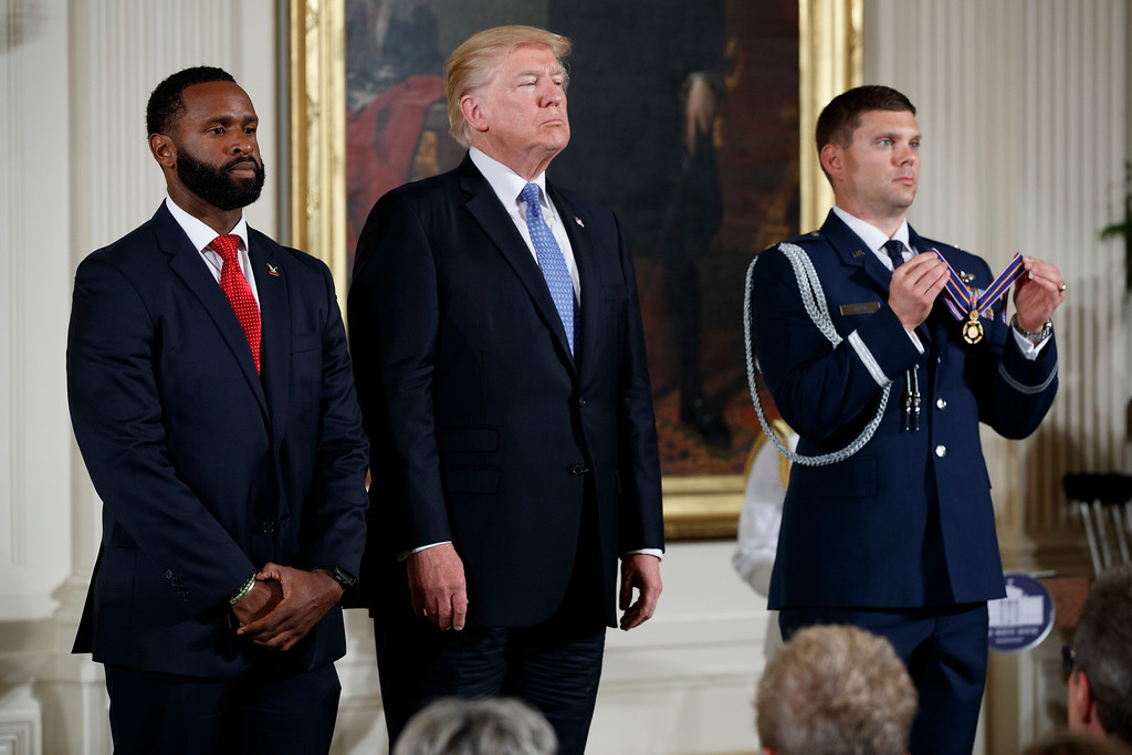 . President Donald Trump stands with Capitol Hill police Officer David Bailey as a citation for the Medal of Valor is read during a ceremony in the East Room of the White House in Washington, Thursday, July 27, 2017, to recognize the first responders from the June 14 Congressional baseball shooting. (AP Photo/Evan Vucci)