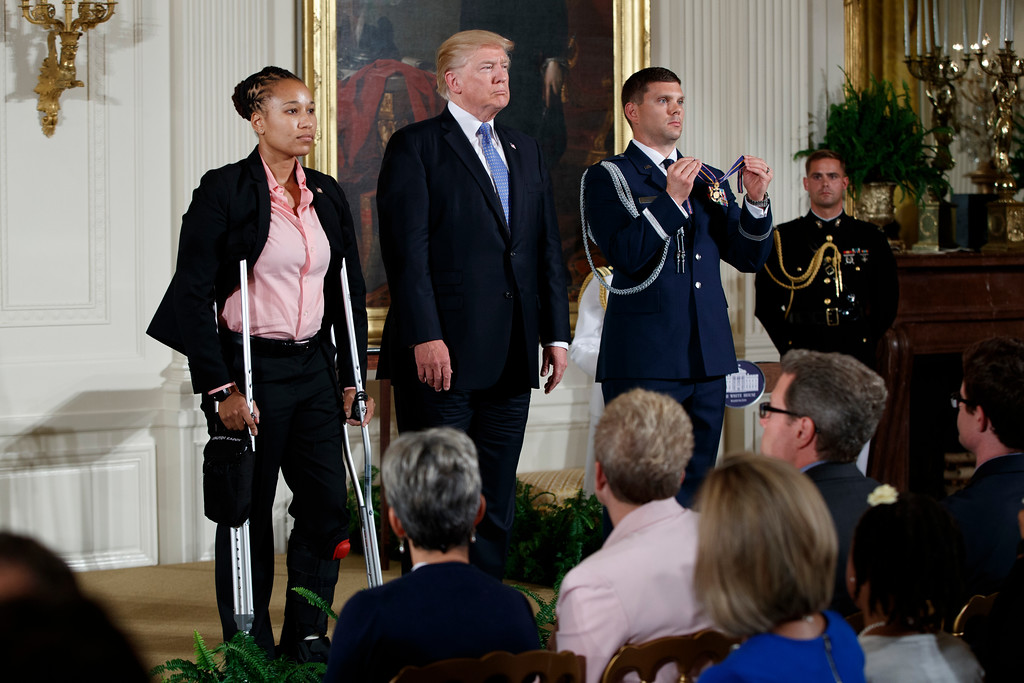 . Capitol Hill police officer Crystal Griner and President Donald Trump listen to the reading of a citation for the Medal of Valor during a ceremony in the East Room of the White House in Washington, Thursday, July 27, 2017, to recognize the first responders from the June 14 Congressional baseball shooting. (AP Photo/Evan Vucci)