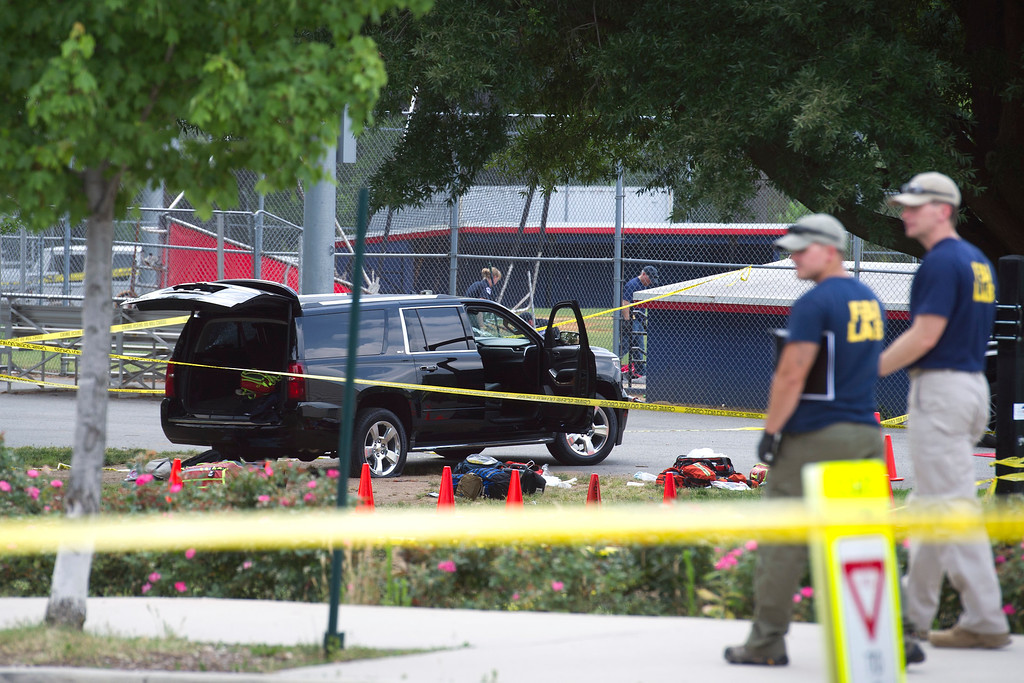 . An SUV, with a bullet hole in the windshield and a flat tire, sits in the parking lot at the scene of a multiple shooting in Alexandria, Va., Wednesday, June 14, 2017, involving House Majority Whip Steve Scalise of La., and others, during a congressional baseball practice. (AP Photo/Cliff Owen)