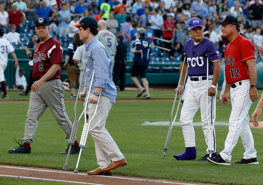 . Injured aide Zach Barth, left, and Rep. Roger Williams, R-Texas, also on crutches walk off the field before the Congressional baseball game, Thursday, June 15, 2017, in Washington. The annual GOP-Democrats baseball game raises money for charity. (AP Photo/Alex Brandon)