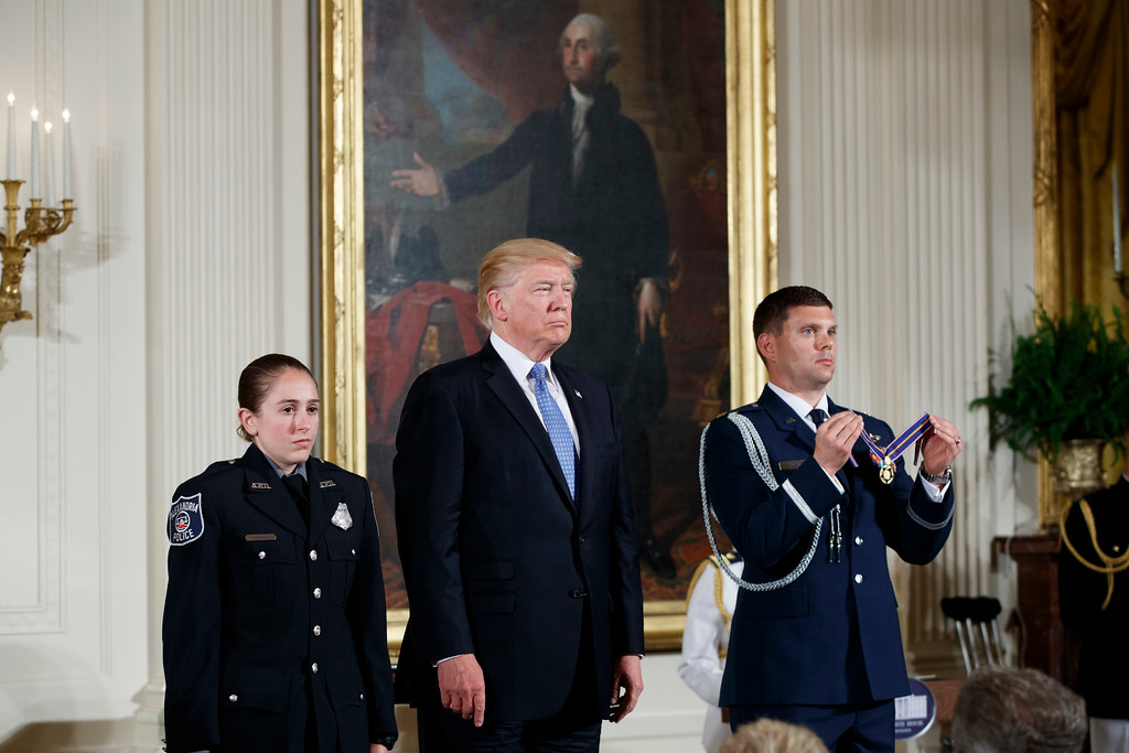 . President Donald Trump stands with Nicole Battaglia of the Alexandria, Va. Police Department as a citation for the Medal of Valor is read during a ceremony in the East Room of the White House in Washington, Thursday, July 27, 2017, to recognize the first responders from the June 14 Congressional baseball shooting. (AP Photo/Evan Vucci)