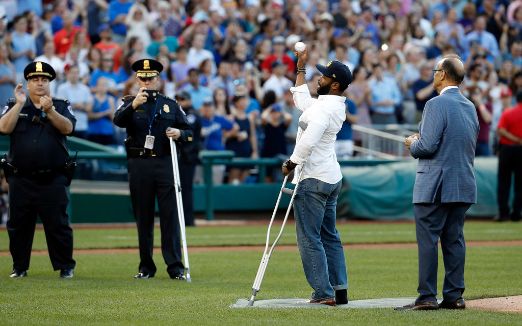 . Injured Capitol Hill Police officer David Bailey throws out a ceremonial first pitch with Joe Torre, MLB\'s Chief Baseball Officer, right, watching, before the Congressional baseball game, Thursday, June 15, 2017, in Washington. The annual GOP-Democrats baseball game raises money for charity. (AP Photo/Alex Brandon)
