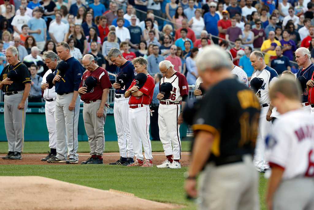 . Members of both congressional teams bow their heads for a moment of silence for Rep. Steve Scalise, R-La., before the Congressional baseball game, Thursday, June 15, 2017, in Washington. The annual GOP-Democrats baseball game raises money for charity. (AP Photo/Alex Brandon)