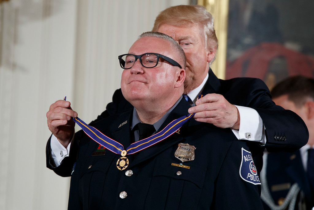 . President Donald Trump presents the Medal of Valor to Kevin Jobe of the Alexandria, Va. Police Department during a ceremony in the East Room of the White House in Washington, Thursday, July 27, 2017, to recognize the first responders from the June 14 Congressional baseball shooting. (AP Photo/Evan Vucci)