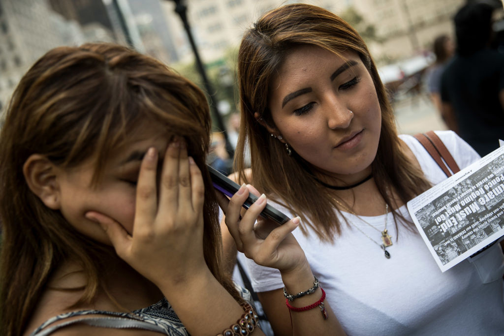 ". NEW YORK, NY - SEPTEMBER 5: (L to R) Paola Soria and Karla Collaguazo, both 20 and ""dreamers\""originally from Ecuador, listen to Attorney General Jeff Sessions\' remarks on ending the Deferred Action for Childhood Arrivals program on a smartphone before a protest in Grand Army Plaza in Manhattan, September 5, 2017. On Tuesday, the Trump administration announced they will end the Deferred Action for Childhood Arrivals program, with a six month delay. The decision represents a blow to young undocumented immigrants (also known as \'dreamers\') who were shielded from deportation under DACA. (Photo by Drew Angerer/Getty Images)"