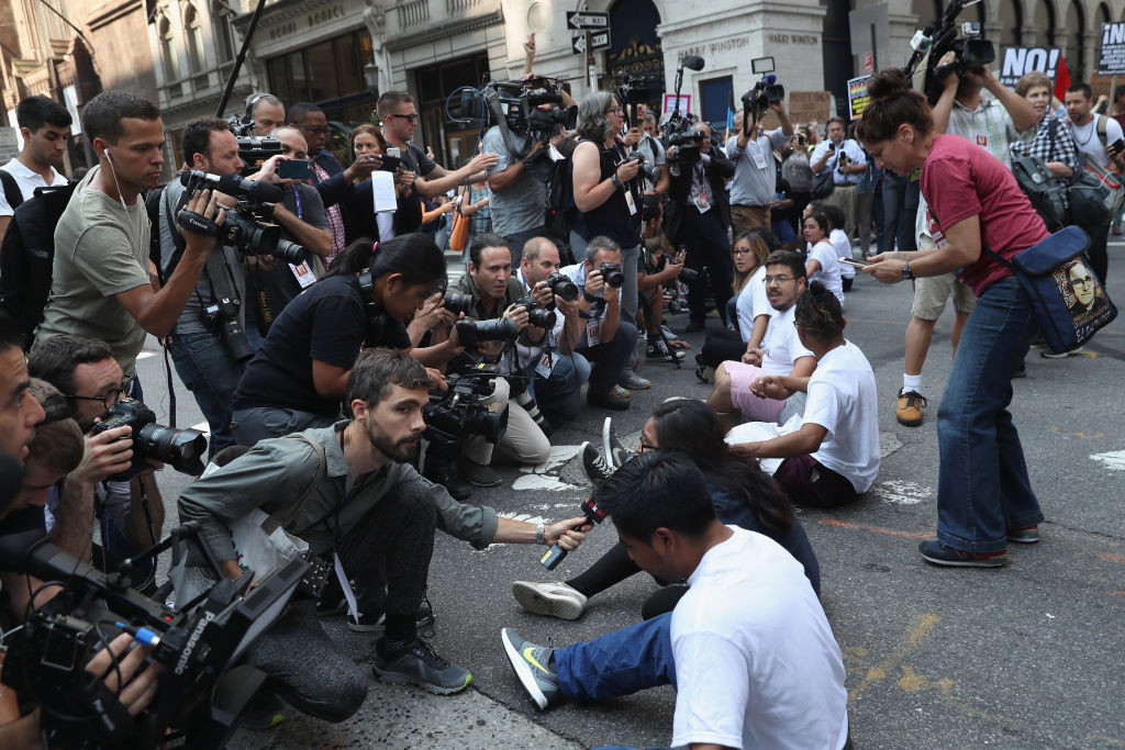". NEW YORK, NY - SEPTEMBER 05:  Journalists photograph ""Dreamer\"" protesters blocking the street in front of Trump Tower on September 5, 2017 in New York City, United States. The Trump administration announced it is ending the Obama-era DACA program that shields young undocumented immigrants from deportation. Up to 800,000 of them brought to the U.S. illegally as children will face possible deportation when the Deferred Action for Childhood Arrivals (DACA) program is set to expire on March 5, 2018.  (Photo by John Moore/Getty Images)"