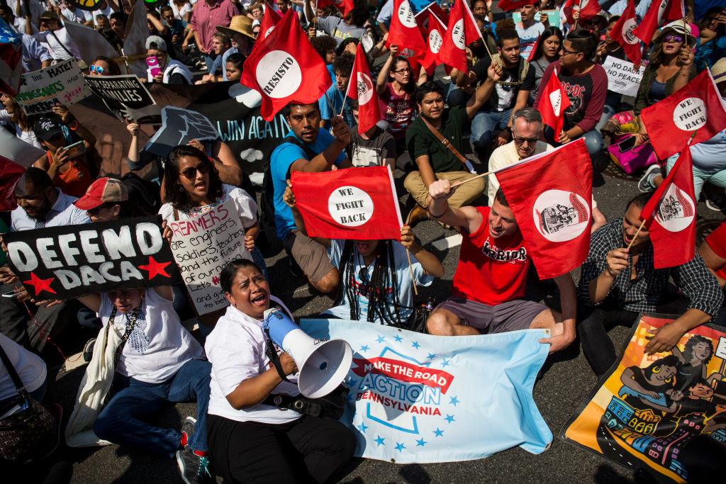 . WASHINGTON, DC - SEPTEMBER 5:  Demonstrators sit on Pennsylvania Avenue during a demonstration in response to the Trump Administration\'s announcement that it would end the Deferred Action for Childhood Arrivals (DACA) program on September 5, 2017 in Washington, DC.  DACA, an immigration policy passed by former President Barack Obama, allows certain undocumented immigrants who arrived in the United States as minors to receive renewable two-year deferred action from deportation and eligibility fork a work permit. (Photo by Zach Gibson/Getty Images)