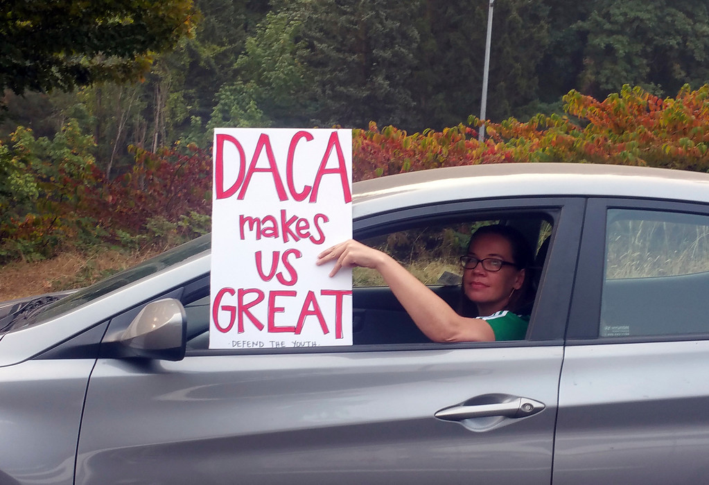 . An unidentified woman holds a sign out her window as she drives through rush hour traffic in Portland, Ore., Tuesday, Sept. 5, 2017.  President Donald Trump on Tuesday began dismantling the Deferred Action for Childhood Arrivals, or DACA, program, the government program protecting hundreds of thousands of young immigrants who were brought into the country illegally as children. (AP Photo/Don Ryan)