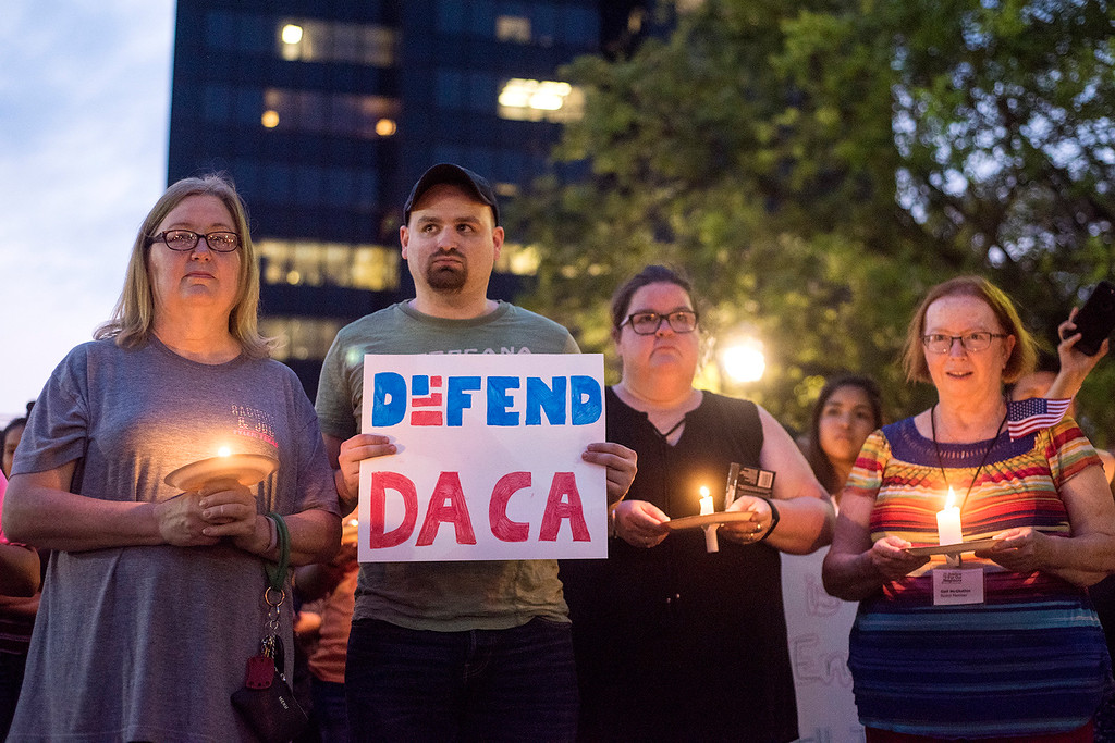 . Martha Waggonner, Walker Waggonner, Katie Powell and Gail McGlothin stand in silence holding candles and signs during a silent vigil in honor of Deferred Action for Childhood Arrivals (DACA) at T.B. Butler Fountain Plaza in Tyler, Texas, on Tuesday, Sept. 5, 2017. Nearly 500 people attended the vigil on the day that the Trump administration announced that they would phase out the program. (Chelsea Purgahn/Tyler Morning Telegraph)