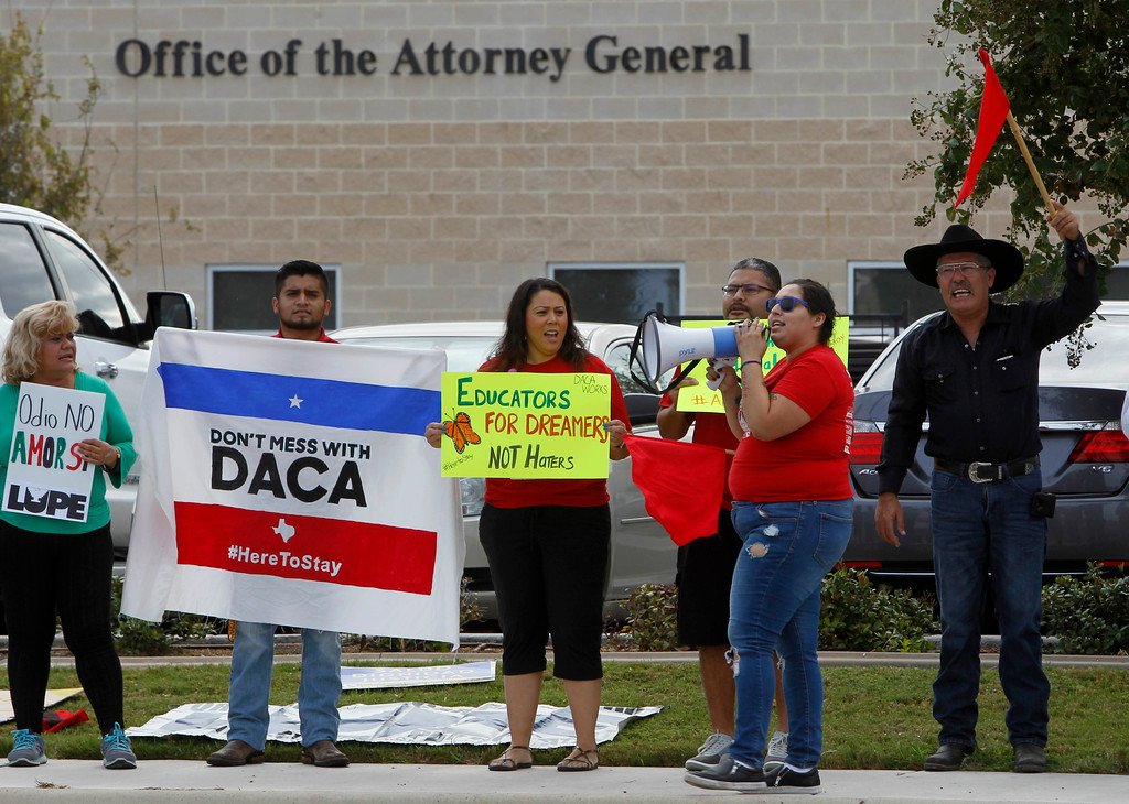 . Abraham Diaz, left, Stephanie Alvarez, center, and Stevie Luna, right with bullhorn, gather in support of DACA, Tuesday September 5, 2017 in front of the Texas Attorney General\'s office in Pharr, Texas. U.S. Attorney General Jeff Sessions announced the end of the DACA program with a six month delay on Tuesday. (Nathan Lambrecht/The Monitor via AP)