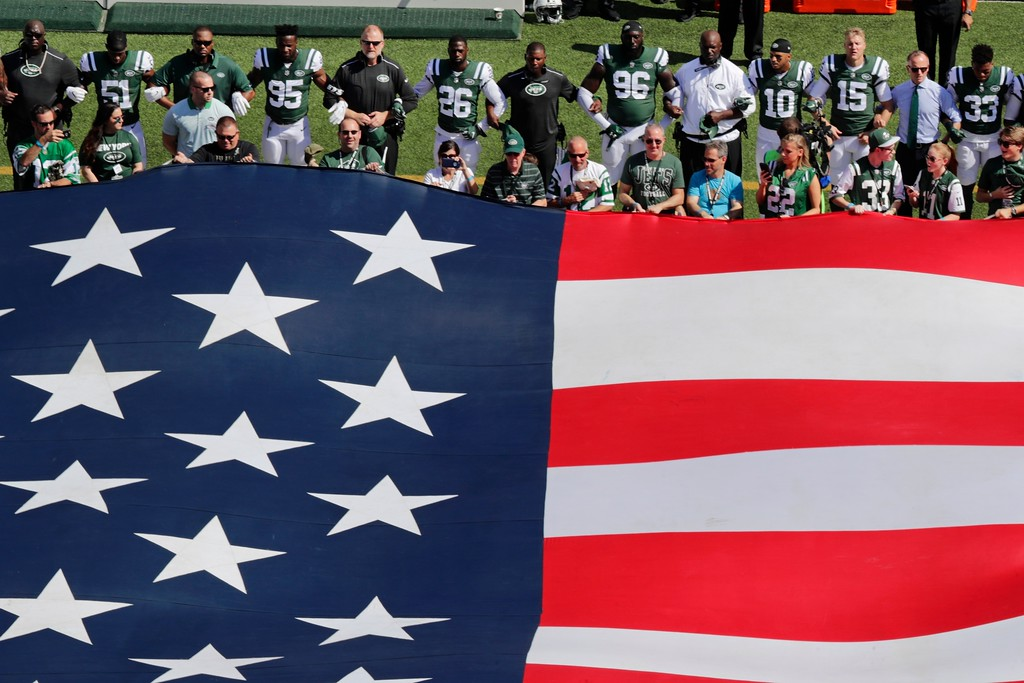 . The New York Jets lock arms during the playing of the national anthem before an NFL football game against the Miami Dolphins Sunday, Sept. 24, 2017, in East Rutherford, N.J. (AP Photo/Frank Franklin II)