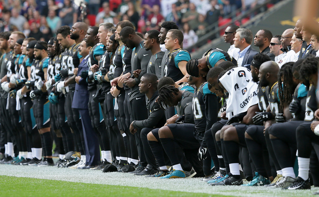 . Jacksonville Jaguars players lock arms and kneel down during the playing of the U.S. national anthem before an NFL football game against the Baltimore Ravens at Wembley Stadium in London, Sunday Sept. 24, 2017. (AP Photo/Tim Ireland)