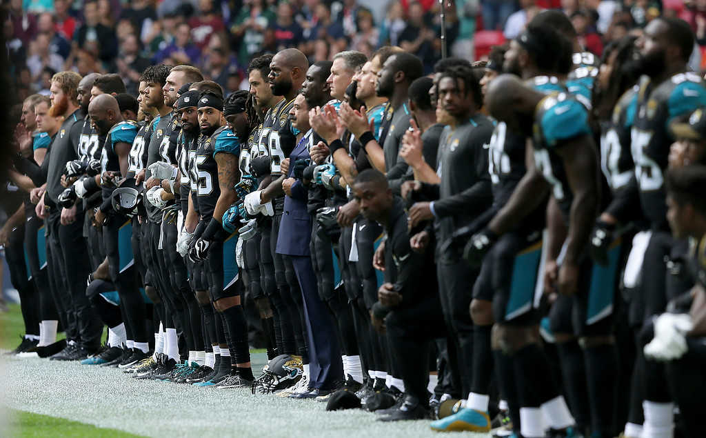. Jacksonville Jaguars owner Shahid Khan, center, joins arms with players as some kneel down during the playing of the U.S. national anthem before an NFL football game against the Baltimore Ravens at Wembley Stadium in London, Sunday Sept. 24, 2017. (AP Photo/Tim Ireland)