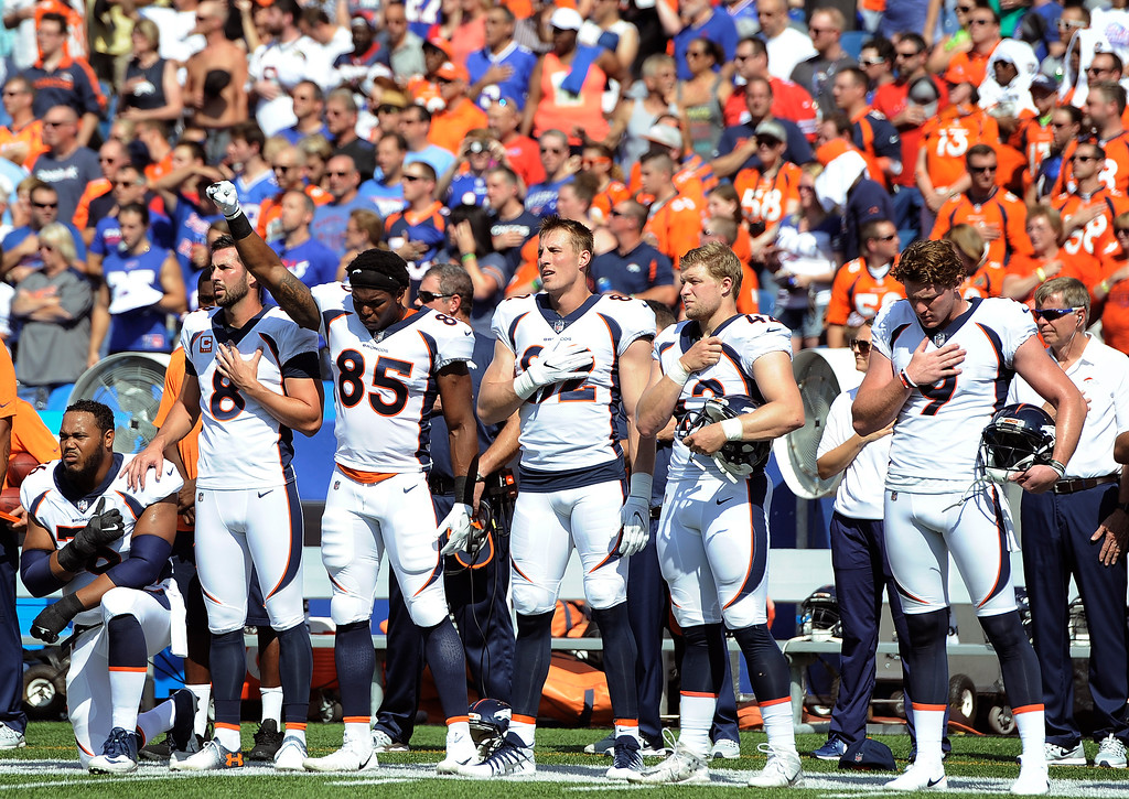 . Denver Broncos tight end Virgil Green (85) gestures as teammate Max Garcia, left, takes a knee during the paying of the national anthem prior to an NFL football game against the Buffalo Bills, Sunday, Sept. 24, 2017, in Orchard Park, N.Y. (AP Photo/Adrian Kraus)