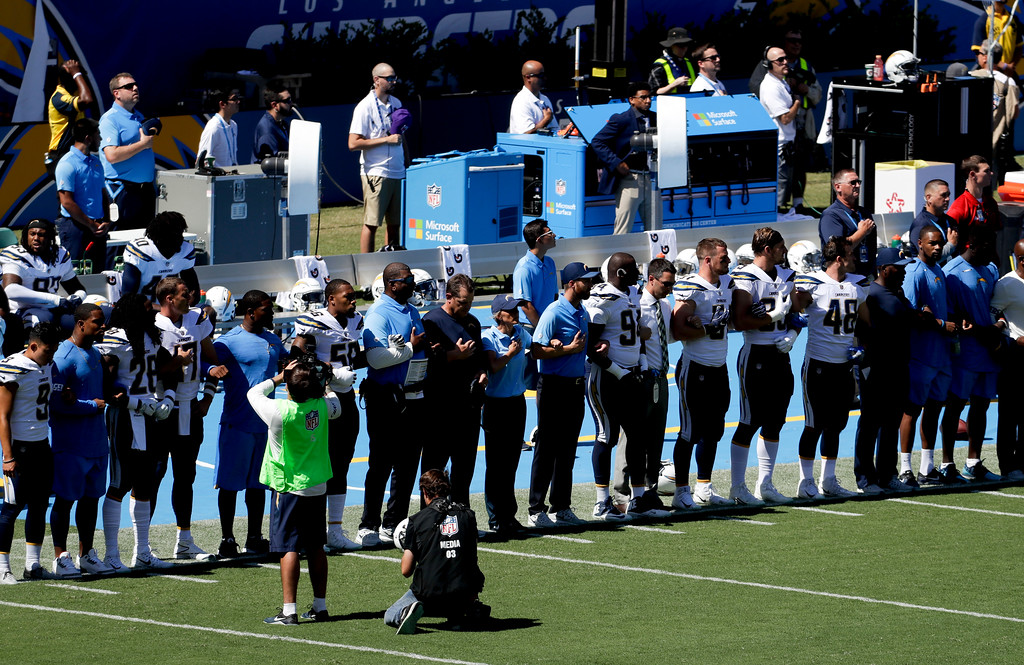 . Members off the Los Angeles Chargers lock arms in protest before an NFL football game against the Kansas City Chiefs Sunday, Sept. 24, 2017, in Carson, Calif. (AP Photo/Chris Carlson)