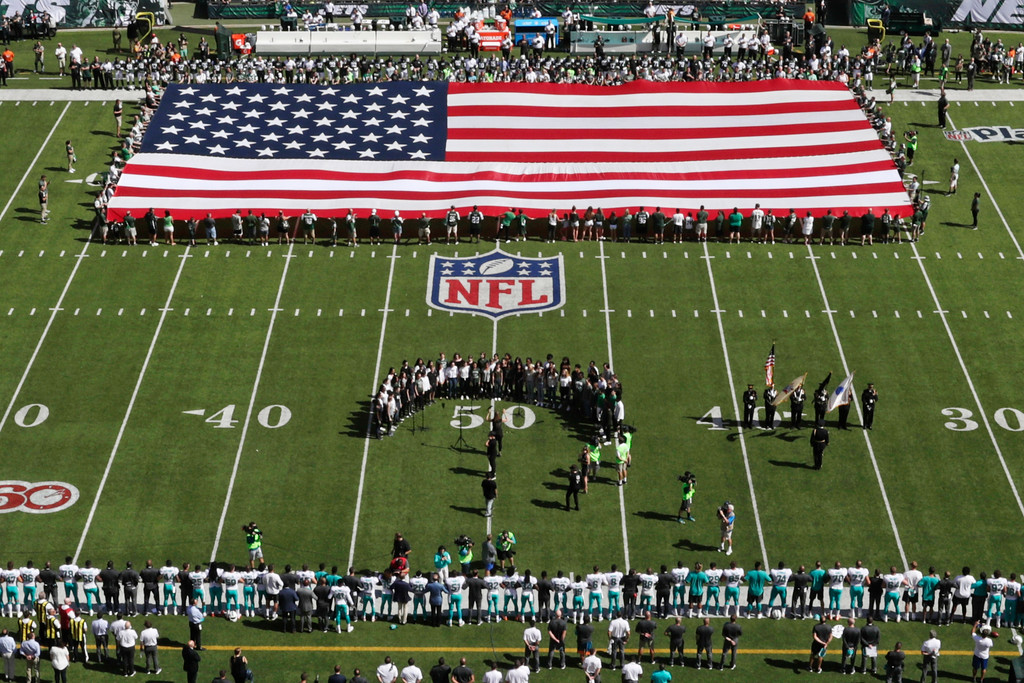 . Players lock arms during the playing of the national anthem before an NFL football game between the New York Jets and the Miami Dolphins Sunday, Sept. 24, 2017, in East Rutherford, N.J. (AP Photo/Frank Franklin II)