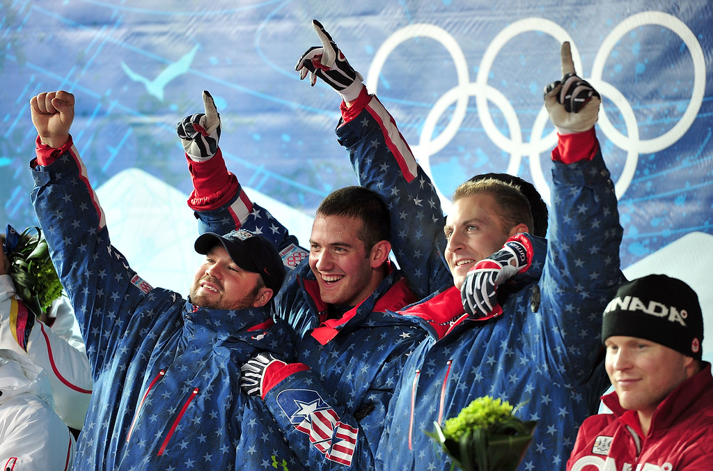 . WHISTLER, BC - FEBRUARY 27:  (L to R) Steven Holcomb, Justin Olsen and Curtis Tomasevicz of USA 1 celebrate after winning the gold medal during the men\'s four man bobsleigh on day 16 of the 2010 Vancouver Winter Olympics at the Whistler Sliding Centre on February 27, 2010 in Whistler, Canada.  (Photo by Clive Mason/Getty Images)