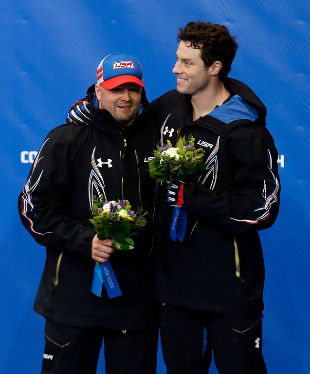 . The team from the United States USA-1, piloted by Steven Holcomb, left, and brakeman Steven Langton, celebrate their bronze medal win after the men\'s two-man bobsled competition at the 2014 Winter Olympics, Monday, Feb. 17, 2014, in Krasnaya Polyana, Russia. (AP Photo/Natacha Pisarenko)