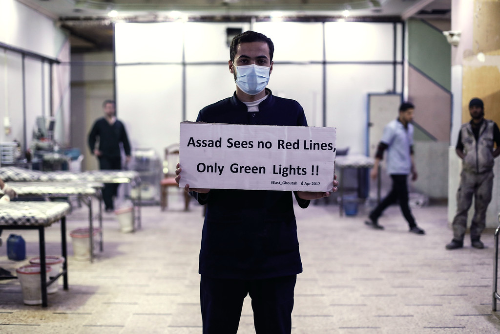 ". A medical staff at Damascus Countryside Specialised Hospital holds a placard condemning a suspected chemical weapons attack on the Syrian town of Khan Sheikhun, during a gathering to show solidarity with the victims in the rebel-held Douma on the outskirts of Damascus on April 6, 2017. US forces fired a barrage of cruise missiles at a Syrian airbase on April 7 in response to what President Donald Trump called a ""barbaric\"" chemical attack he blamed on the Damascus regime. Syria\'s regime has denied any use of chemical weapons and state media on Friday described the US strike -- which was reported to have pulverised the base and killed at least four servicemen -- as an \""act of aggression\"". (SAMEER AL-DOUMY/AFP/Getty Images)"