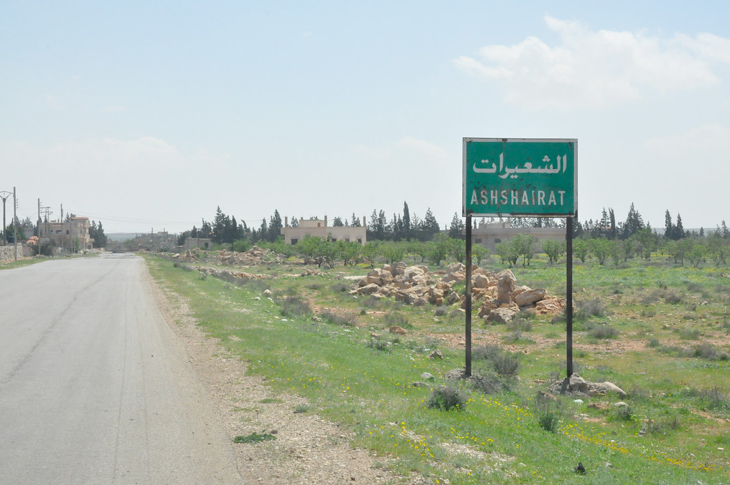 ". A picture taken on April 7, 2017 shows a sign with the name of the village of Shayrat (""ash-Shairat\"") at its entrance, near the Syrian government forces military base which was targeted earlier overnight by US Tomahawk cruise missiles, southeast of the central and third largest Syrian city of Homs. (STRINGER/AFP/Getty Images)"