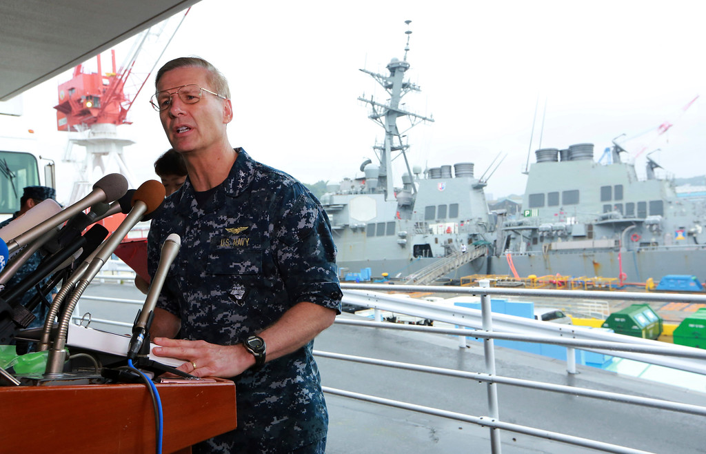 . Vice Adm. Joseph Aucoin, Commander of the U.S. 7th Fleet, speaks during a press conference on the status of USS Fitzgerald, seen at the rear,  and search and rescue efforts for seven missing Fitzgerald crew members at the U.S. Naval base in Yokosuka, southwest of Tokyo Sunday, June 18, 2017. (AP Photo/Eugene Hoshiko)