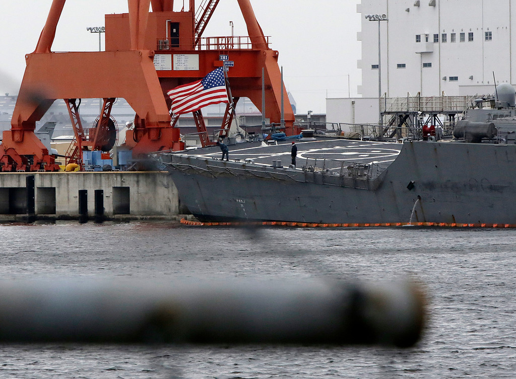 . Staffs stand near the U.S flag of damaged USS Fitzgerald seen at the U.S. Naval base in Yokosuka, southwest of Tokyo Sunday, June 18, 2017.  Navy divers found a number of sailors\' bodies Sunday aboard the stricken USS Fitzgerald that collided with a container ship Saturday in the busy sea off Japan.  (AP Photo/Eugene Hoshiko)