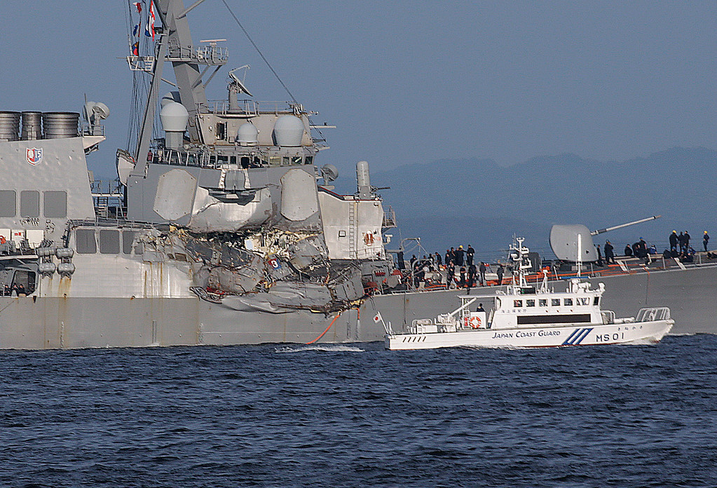 . A Japan Coast Guard ship, foreground, navigates the damaged USS Fitzgerald near the U.S. Naval base in Yokosuka, southwest of Tokyo, after the U.S. destroyer collided with the Philippine-registered container ship ACX Crystal in the waters off the Izu Peninsula Saturday, June 17, 2017. The USS Fitzgerald was back at its home port in Japan after colliding before dawn Saturday with a container ship four times its size, while the coast guard and Japanese and U.S. military searched for seven sailors missing after the crash. (AP Photo/Eugene Hoshiko)