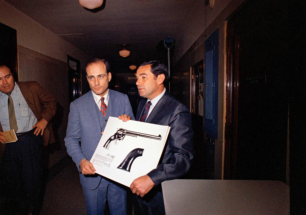 . Deputy District Attorneys Vincent Bugliosi, left, and Aaron Stovitz, holding picture of gun, talk to the press at the L.A. County courthouse during the county grand jury hearings on the Sharon Tate murders, Dec. 1969.   (AP Photo)