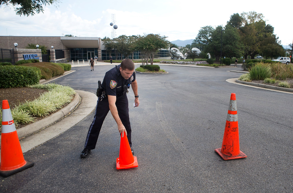 . A Roanoke police officer moves road cones back into position after letting a vehicle through at WDBJ\'s Digital Broadcast Center, Wednesday, Aug. 26, 2015, in Roanoke, Va. Two of the station\'s journalists were fatally shot while doing an on-air broadcast earlier in the day at Bridgewater Plaza in Moneta, Va. (Erica Yoon/The Roanoke Times via AP)