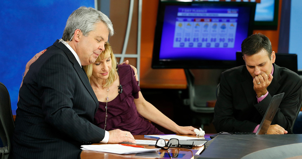 . WDBJ-TV7 news morning anchor Kimberly McBroom, center, gets a hug from visiting anchor Steve Grant, left, as meteorologist Leo Hirsbrunner reflects after their early morning newscast at the station, Thursday, Aug. 27, 2015, in Roanoke, Va. Reporter Alison Parker and cameraman Adam Ward were killed during a live broadcast Wednesday, while on assignment in Moneta. (AP Photo/Steve Helber)