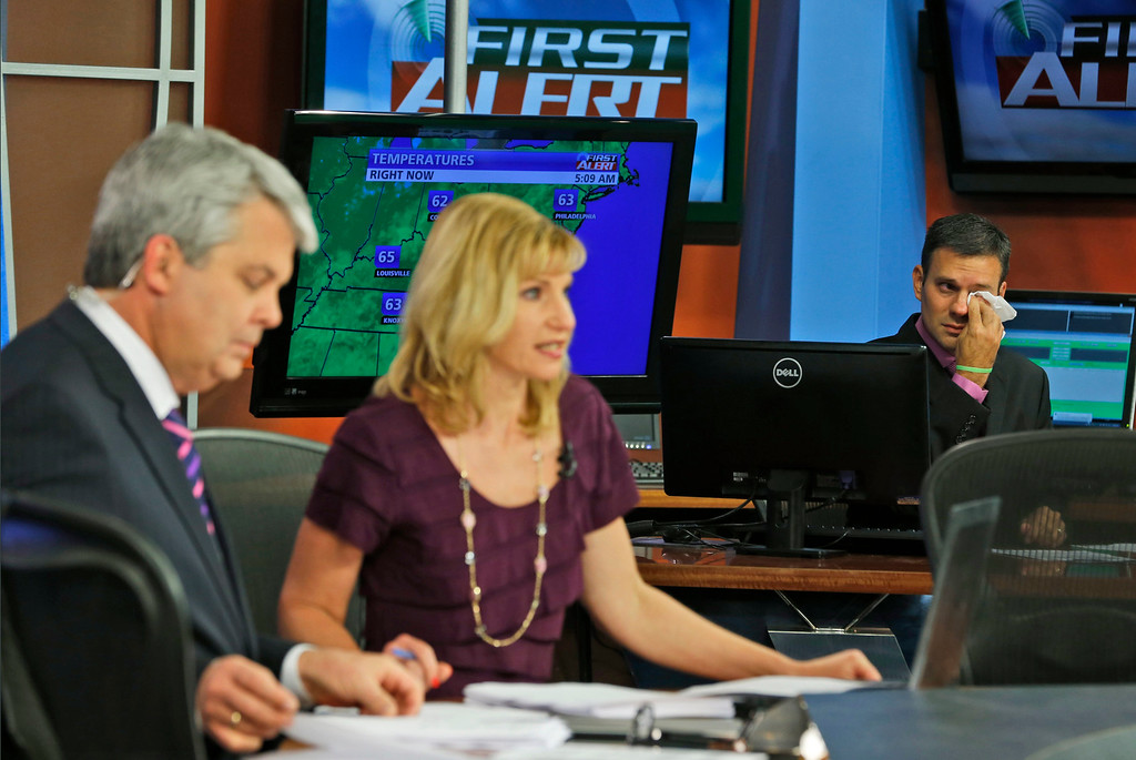 . WDBJ-TV7 meteorologist Leo Hirsbrunner, right, wipes his eyes during the early morning newscast as anchors Kimberly McBroom, center, and guest anchor Steve Grant deliver the news at the station in Roanoke, Va., Thursday, Aug. 27, 2015. Reporter Alison Parker and cameraman Adam Ward were killed during a live broadcast Wednesday, while on assignment in Moneta. (AP Photo/Steve Helber)