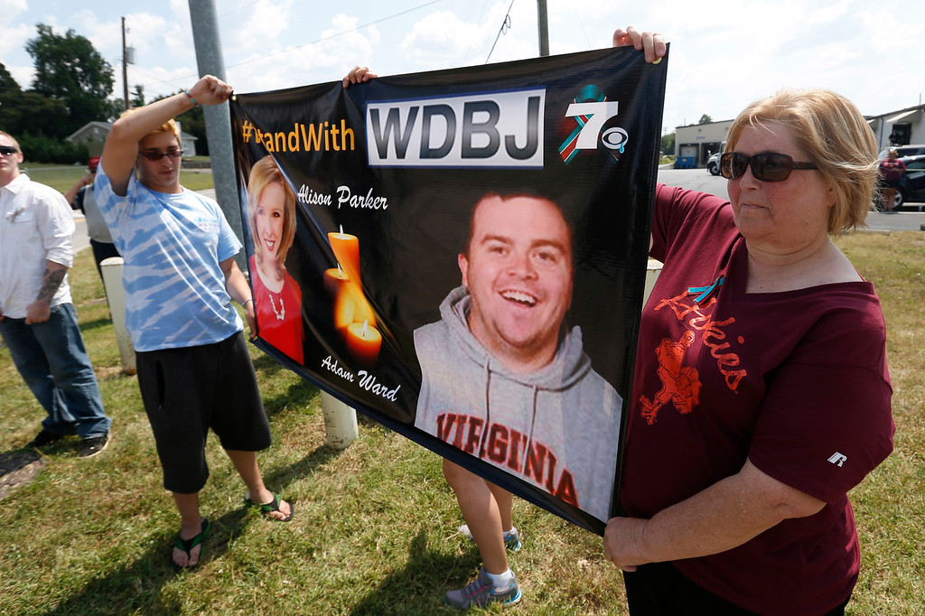 . Local residents Hunter Cregger, left, and his mother Sandra Cregger, show their support for WDBJ-TV cameraman Adam Ward at the Blue Ridge Memorial Garden cemetery in Roanoke, Va., Tuesday, Sept. 1, 2015. Ward and WDBJ-TV morning reporter Alison Parker were fatally shot by a former co-worker on live television during an interview on Aug. 26. (AP Photo/Steve Helber)