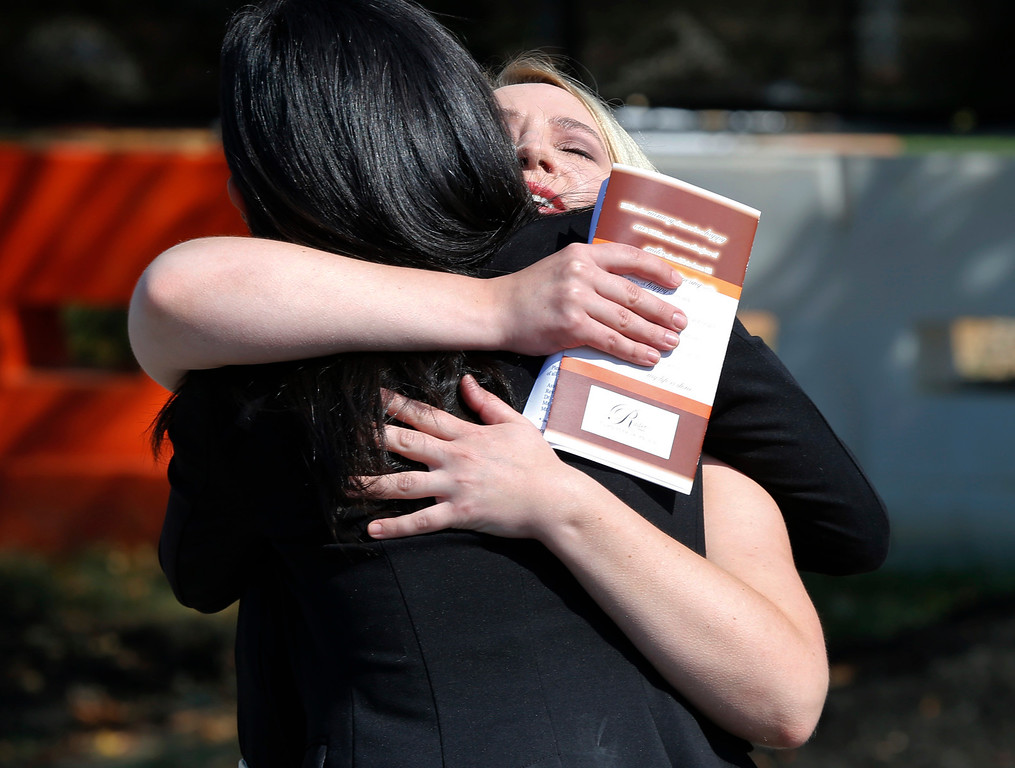 . Amanda Kenney, right, a reporter for WDBJ-TV7, hugs a friend prior to the funeral for cameraman Adam Ward at First Baptist Church in Roanoke, Va., Tuesday, Sept. 1, 2015. Ward and morning reporter Alison Parker were fatally shot by a former co-worker on live television during an interview on Aug. 26. (AP Photo/Steve Helber)