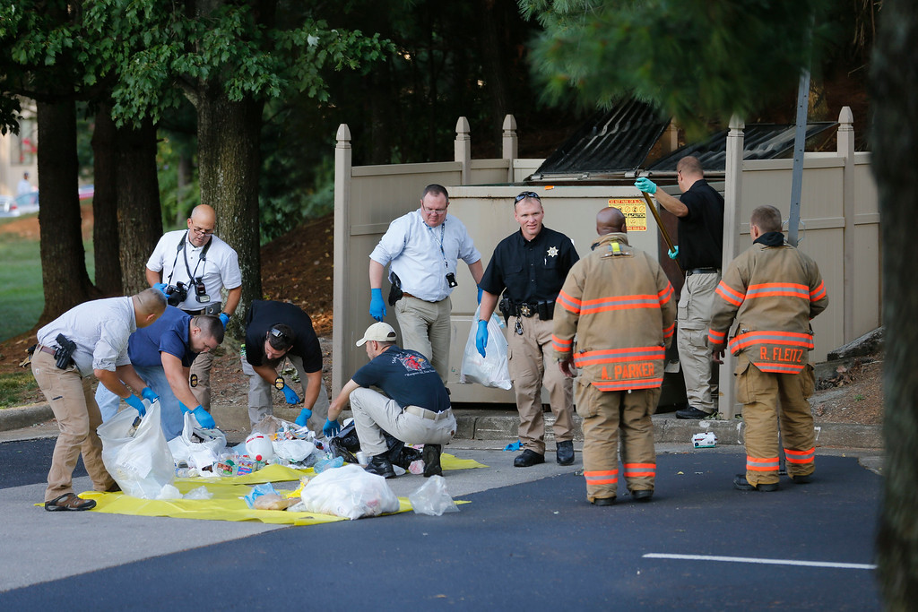 . Investigators search garbage from a dumpster near the apartment of Vester Lee Flanagan II, in Roanoke, Va., Wednesday, Aug. 26, 2015.  Flanagan filmed himself gunning down a WDBJ-TV reporter and cameraman during a live broadcast Wednesday and posted the video on social media after fleeing the scene.  (AP Photo/Steve Helber)