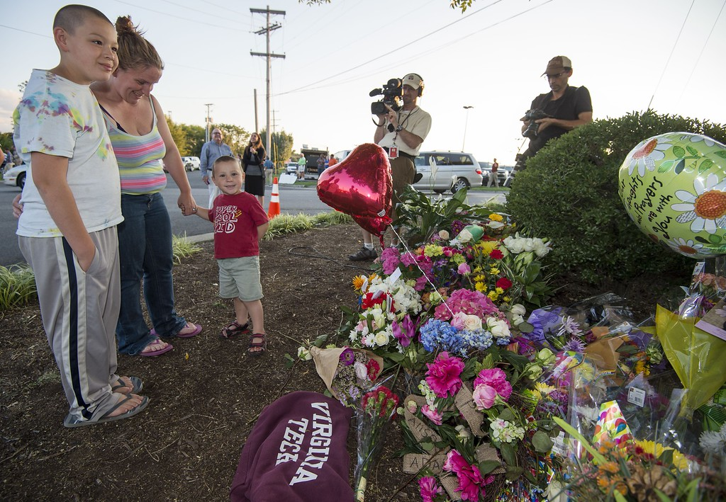 . Members of the Stump family pay their respects at a makeshift memorial for reporter Alison Parker, 24, and cameraman Adam Ward, 27, at the gate of WDBJ television studios August 26, 2015,  in Roanoke, Virginia. Former reporter Vester Lee Flanagan fired by Virginia television station WDBJ shot dead the two journalists during a live broadcast Wednesday and posted chilling footage of the crime online before fatally shooting himself.            (PAUL J. RICHARDS/AFP/Getty Images)