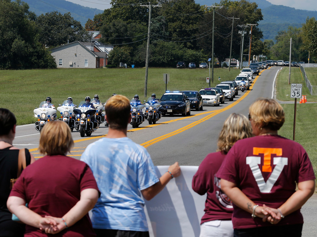 . Local residents show their support at for WDBJ-TV cameraman Adam Ward as the procession from his funeral arrives at the Blue Ridge Memorial Garden cemetery in Roanoke, Va., Tuesday, Sept. 1, 2015. Ward and WDBJ-TV morning reporter Alison Parker were fatally shot by a former co-worker on live television during an interview on Aug. 26.  (AP Photo/Steve Helber)