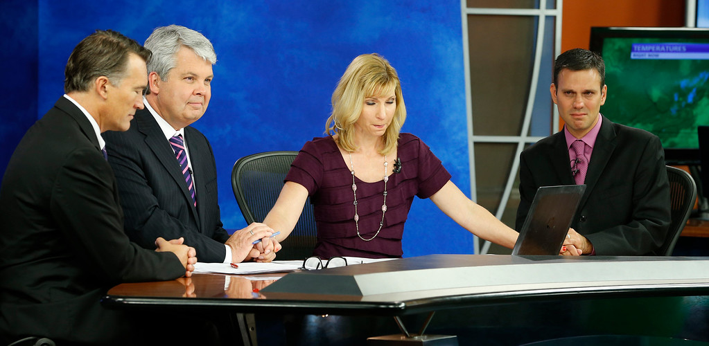 . WDBJ-TV7 news morning anchor Kimberly McBroom, second from right, and meteorologist Leo Hirsbrunner, right, are joined by visiting anchor Steve Grant, second from left, and Dr. Thomas Milam, of the Carilion Clinic, as they observe a moment of silence during the early morning newscast at the station, in Roanoke, Va., Thursday, Aug. 27, 2015. The moment of silence was at the moment reporter Alison Parker and cameraman Adam Ward were killed during a live broadcast Wednesday, while on assignment in Moneta. (AP Photo/Steve Helber)