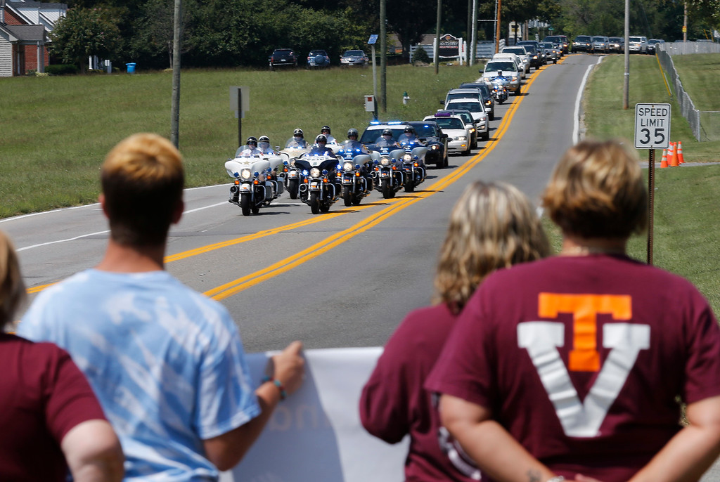 . Local residents show their support at for WDBJ-TV cameraman Adam Ward as the procession from his funeral arrives at the Blue Ridge Memorial Garden cemetery in Roanoke, Va., Tuesday, Sept. 1, 2015. Ward and morning reporter Alison Parker were fatally shot by a former co-worker on live television during an interview on Aug. 26.  (AP Photo/Steve Helber)
