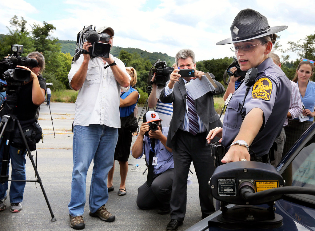 . Virginia State Trooper Pamela Neff points out the license plate recognition equipment on her cruiser that identified the car used by alleged on-air gunman Vester Flanagan Wednesday Aug. 26, 2015 in Markam, Va. A TV reporter and cameraman were shot to death on live television Wednesday by Flanagan their former colleague, a journalist who also recorded himself carrying out the killings and then posted the video on social media. (Scott Mason/The Winchester Star via AP)
