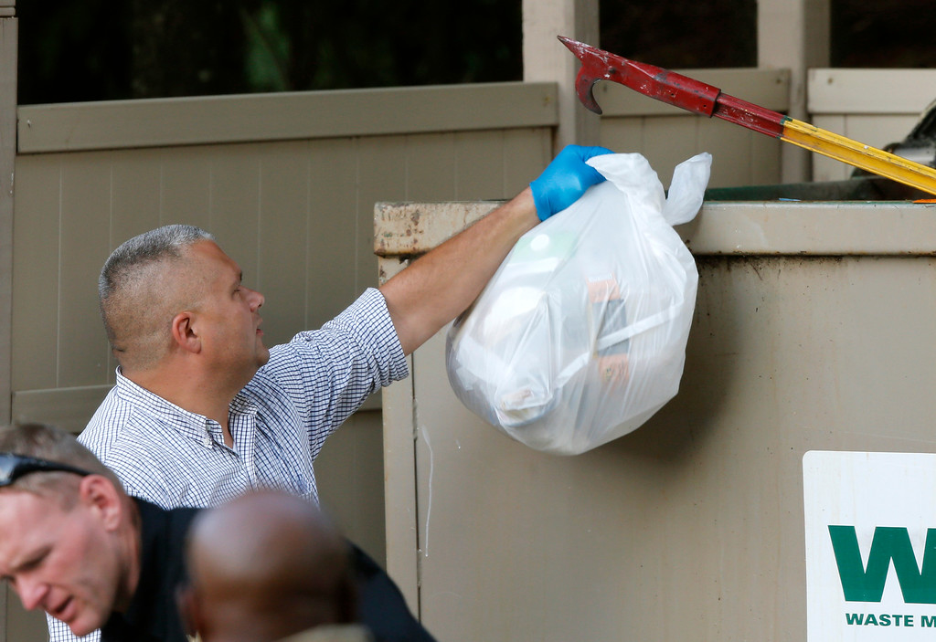 . Investigators search garbage from a dumpster near the apartment of Vester Lee Flanagan II in Roanoke, Va., Wednesday, Aug. 26, 2015.  Flanagan filmed himself gunning down a WDBJ-TV reporter and cameraman during a live broadcast Wednesday and posted the video on social media after fleeing the scene.  (AP Photo/Steve Helber)