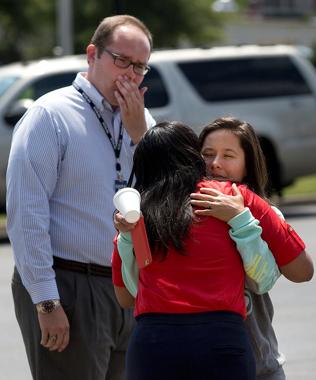 . Reporter Whitney Delbridge hugs WDBJ7 news anchor and reporter Melissa Gaona after journalists Alison Parker and Adam Ward were killed as Justin Ward, New River Valley Bureau Chief for WDBJ7, looks on in Roanoke, Va., Wednesday, Aug. 26, 2015. Vester Lee Flanagan opened fire during a live on-air interview for WDBJ7, killing the two journalists Wednesday. (Erica Yoon/The Roanoke Times via AP)