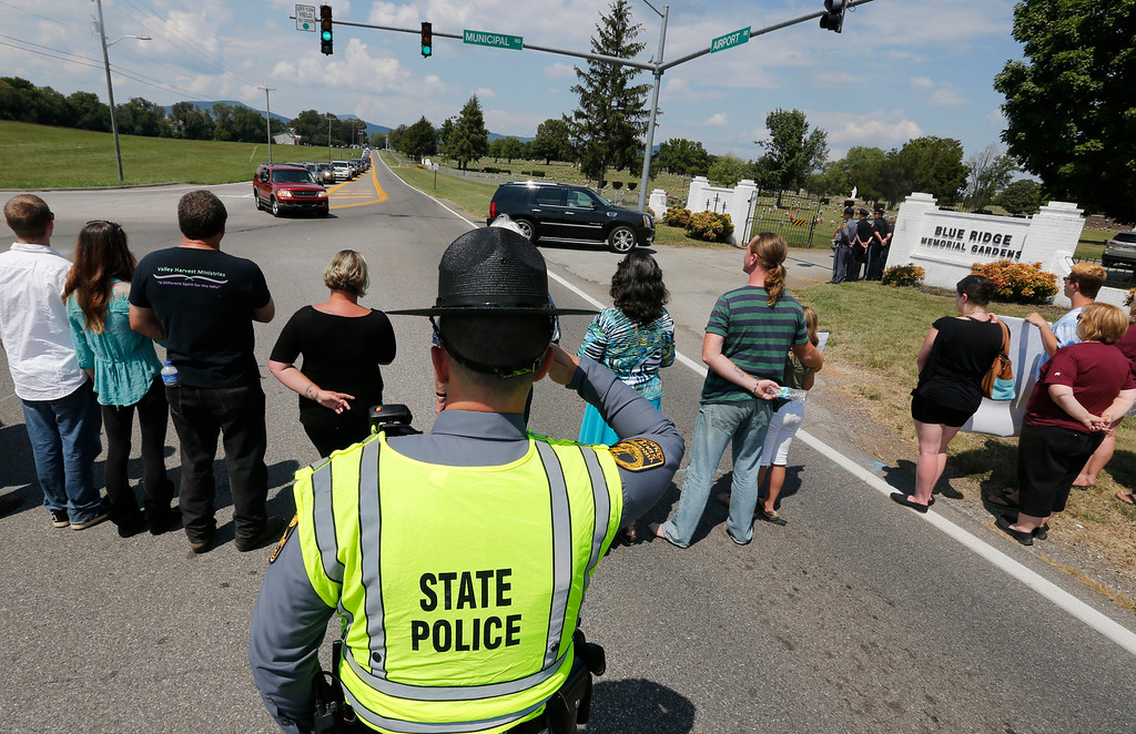 . A Virginia state trooper salutes as mourners at the funeral for WDBJ-TV cameraman Adam Ward arrive at the Blue Ridge Memorial Garden cemetery in Roanoke, Va., Tuesday, Sept. 1, 2015.  Ward and morning reporter Alison Parker were fatally shot by a former co-worker on live television during an interview on Aug. 26. (AP Photo/Steve Helber)