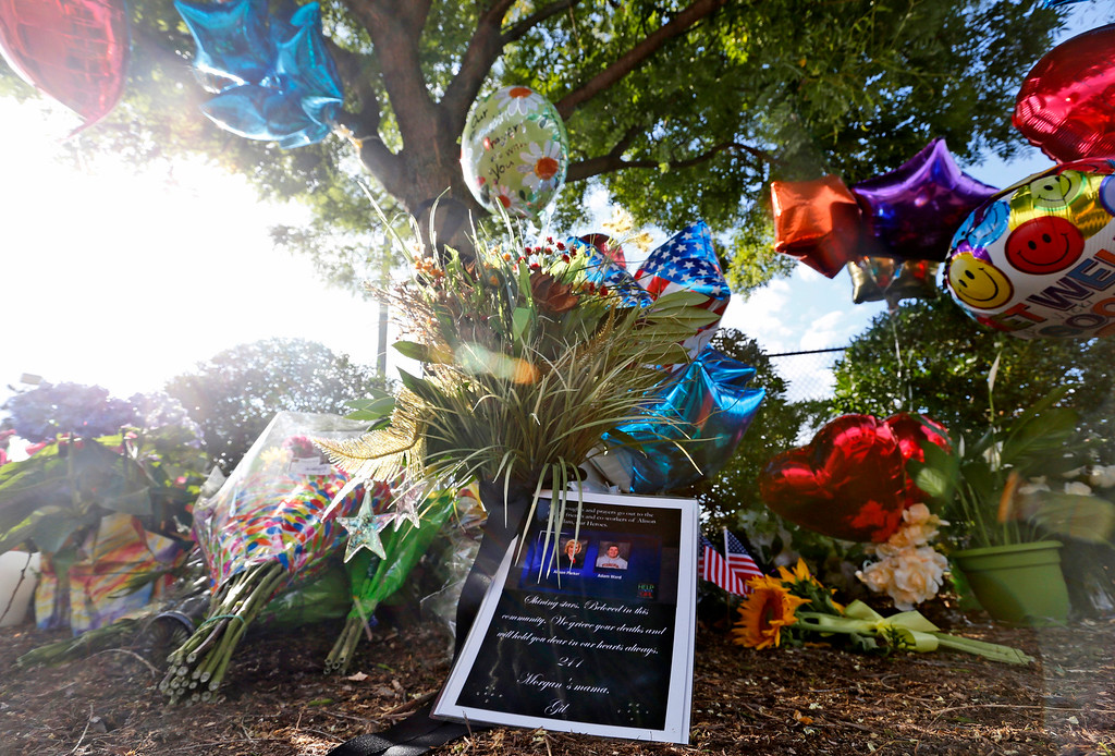 . A makeshift memorial is assembled in front of WDBJ television station in Roanoke, Va., Wednesday, Aug. 26, 2015.  A WDBJ- TV reporter and cameraman were shot to death during a live television interview Wednesday by a gunman who recorded himself carrying out the killings and posted the video on social media after fleeing the scene.  (AP Photo/Steve Helber)