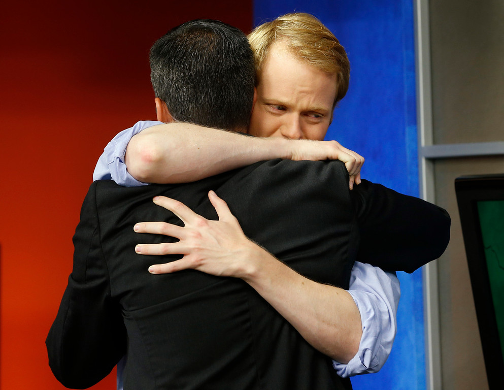 . WDBJ-TV7 anchor Chris Hurst, right, hugs meteorologist Leo Hirsbrunner during the early morning newscast at WDBJ-TV7, in Roanoke, Va., Thursday, Aug. 27, 2015. Hurst was the fiance of Alison Parker, who was killed during a live broadcast Wednesday, in Moneta. (AP Photo/Steve Helber)