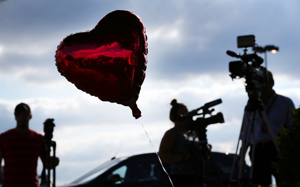. Reporters gather around a memorial of balloons and flowers placed outside of  WDBJ7\'s Digital Broadcast Center in Roanoke, Va., Wednesday, Aug. 26, 2015. The shooting of a television reporter and a cameraman unfolded on live TV before an audience of tens of thousands on the smaller market central Virginia television station. (Heather Rousseau/The Roanoke Times via AP)