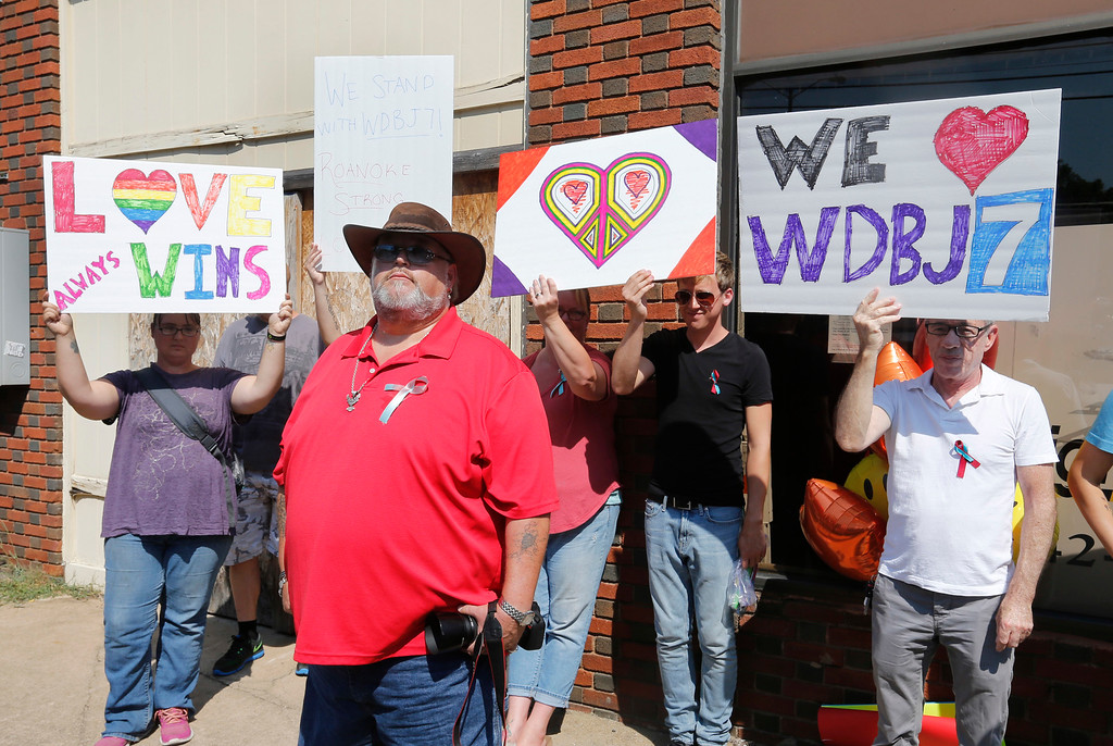 . A demonstrator, front, stands in front of a group of individuals supporting WDBJ-TV during the funeral for WDBJ-TV cameraman Adam Ward at the First Baptist church in Roanoke, Va., Tuesday, Sept. 1, 2015.  The demonstrator objected to content of some of the signs.   Ward and WDBJ-TV morning reporter Alison Parker were fatally shot by a former co-worker on live television during an interview on Aug. 26.  (AP Photo/Steve Helber)