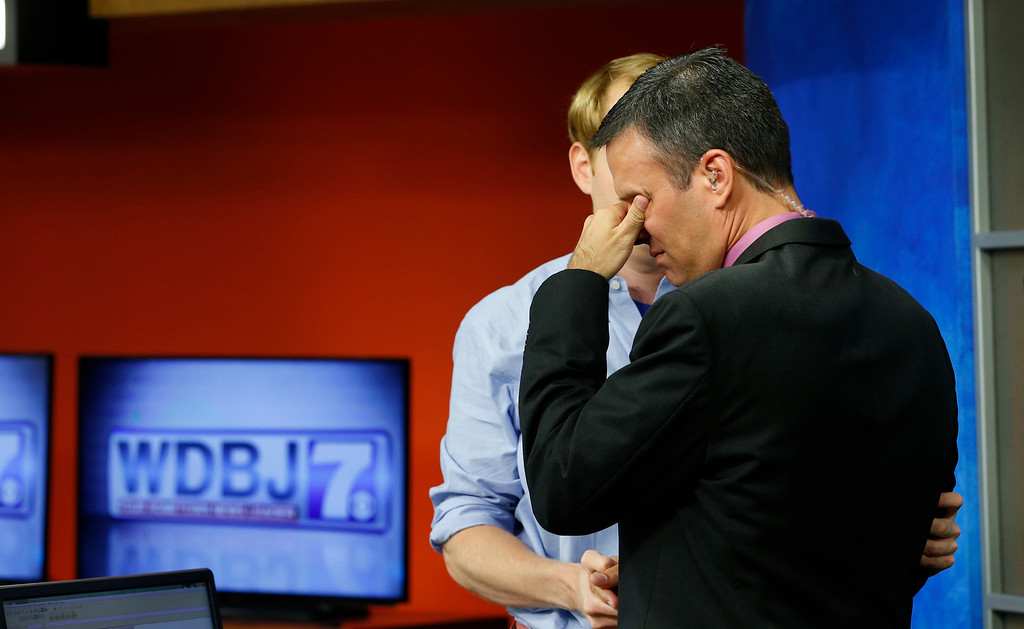 . WDBJ-TV7 anchor Chris Hurst, left, comforts meteorologist Leo Hirsbrunner during the early morning newscast at the station, in Roanoke, Va., Thursday, Aug. 27, 2015. Hurst was the fiance of Alison Parker, who was killed during a live broadcast Wednesday, in Moneta. (AP Photo/Steve Helber)