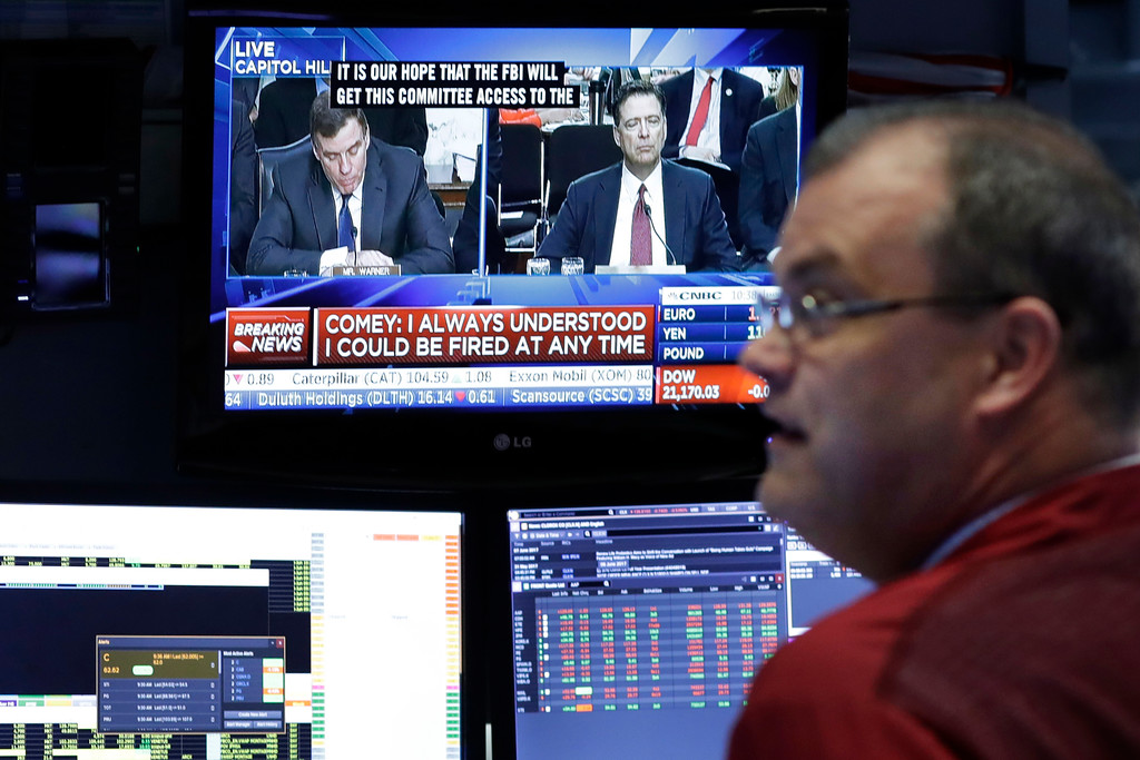 . A stock trader at the New York Stock Exchange watches former FBI Director James Comey on a television monitor, Thursday, June 8, 2017, as Comey testifies before a congressional committee in Washington. (AP Photo/Mark Lennihan)