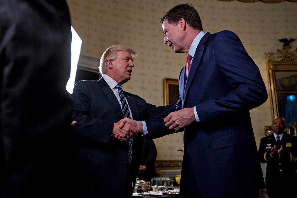 . File - U.S. President Donald Trump (C) shakes hands with James Comey, director of the Federal Bureau of Investigation (FBI), during an Inaugural Law Enforcement Officers and First Responders Reception in the Blue Room of the White House on January 22, 2017 in Washington, DC. In a statement released Tuesday, May 9, Trump says Comey�s firing �will mark a new beginning� for the FBI. (Photo by Andrew Harrer-Pool/Getty Images)