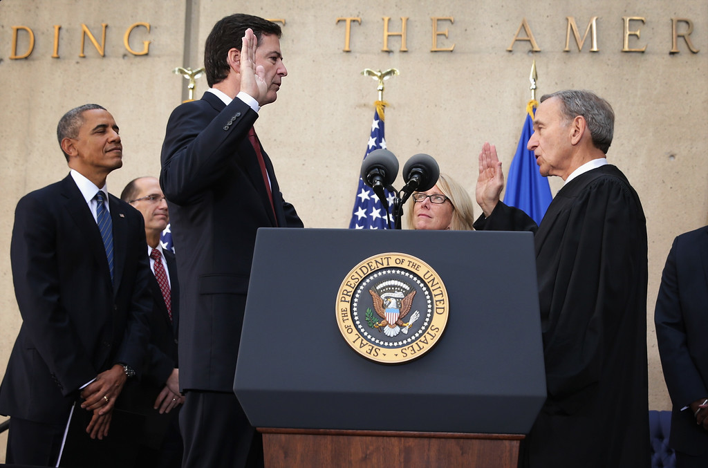 . WASHINGTON, DC - OCTOBER 28:  FBI Director James Comey (3rd L) participates in a ceremonial swearing-in, officiated by Judge John Walker (R), as his wife Patrice (4th L), U.S. President Barack Obama (L), Deputy FBI Director Sean Joyce (2nd L) and Rev. Robert Dortch (R) look on at the FBI Headquarters October 28, 2013 in Washington, DC. Comey was officially sworn in as director of FBI on September 4 to succeed Robert Mueller who had served as director for 12 years.  (Photo by Alex Wong/Getty Images)